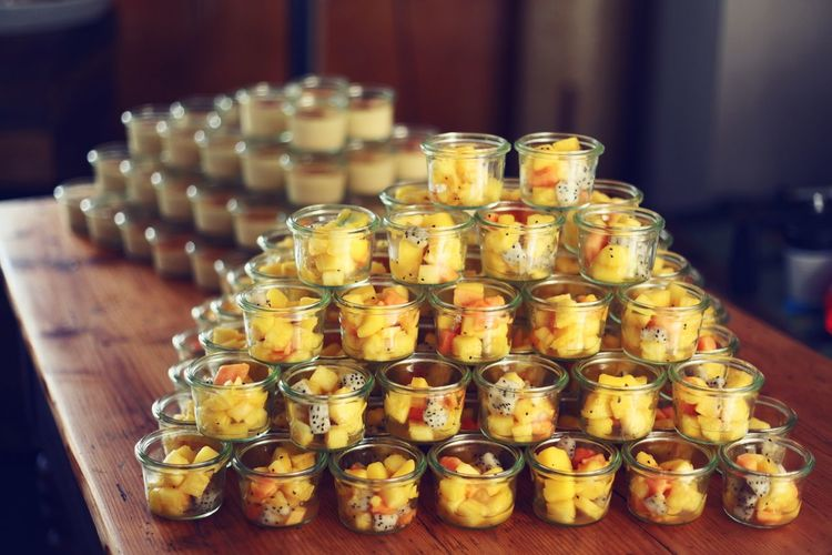 Chopped fruits in containers arranged on table
