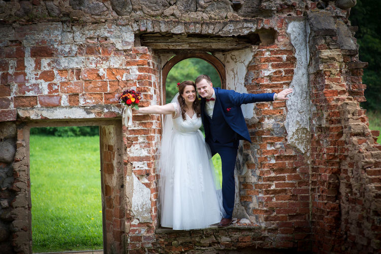 Bride And Groom Standing On Abandoned Wall