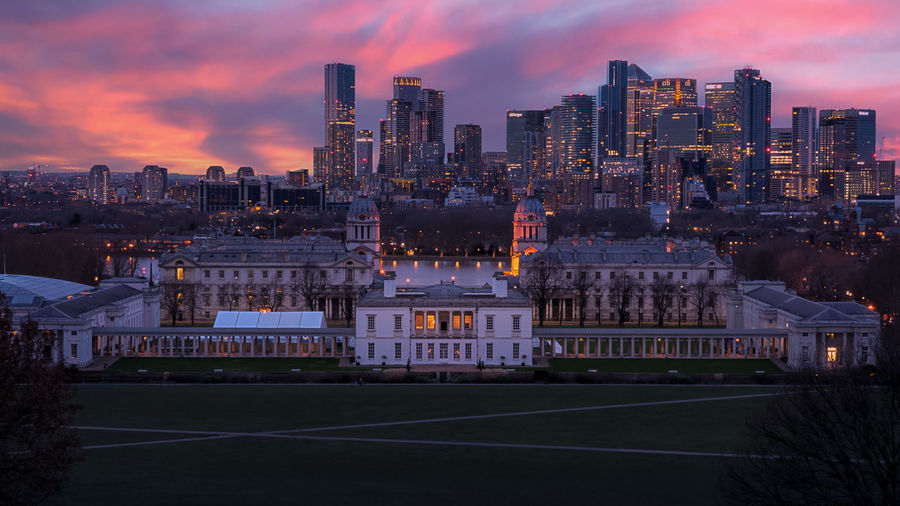 Illuminated buildings in city at sunset