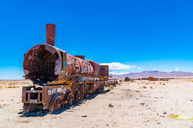 Abandoned train on beach against blue sky