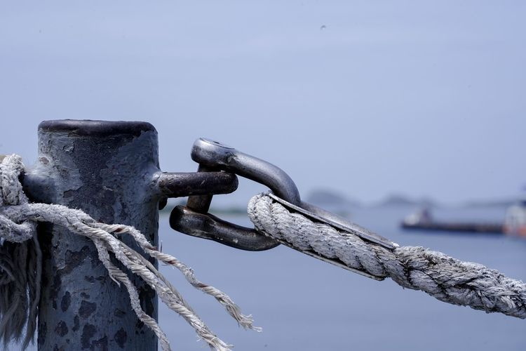 Close-up of rope tied on metal chain against sky