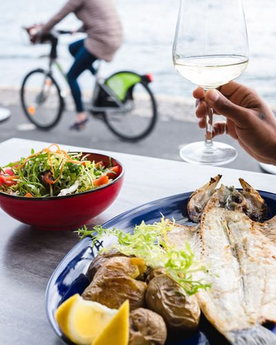 Bicycle View Eating Eating Healthy Eating Out View Fish Wine Wineglass Wine moments Human Hand Men Healthy Lifestyle Bicycle Vegetable Plate Close-up Food And Drink Prepared Food Serving Size Salad Bowl Ready-to-eat Greek Salad Dish Salad