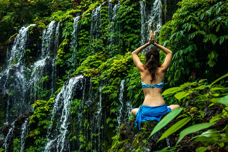 Rear view of woman meditating against waterfall