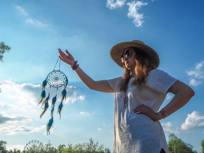 Dreamcatcher in the sky Dreamcatcher Sky Cloud - Sky Hat Real People One Person Women Lifestyles Nature Day Adult Females Standing Outdoors