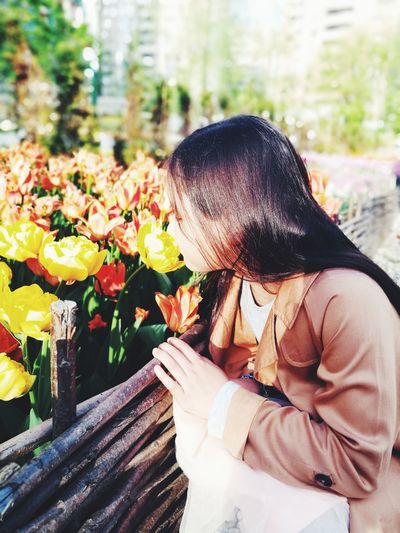 Close-up of girl smelling flowers outdoors