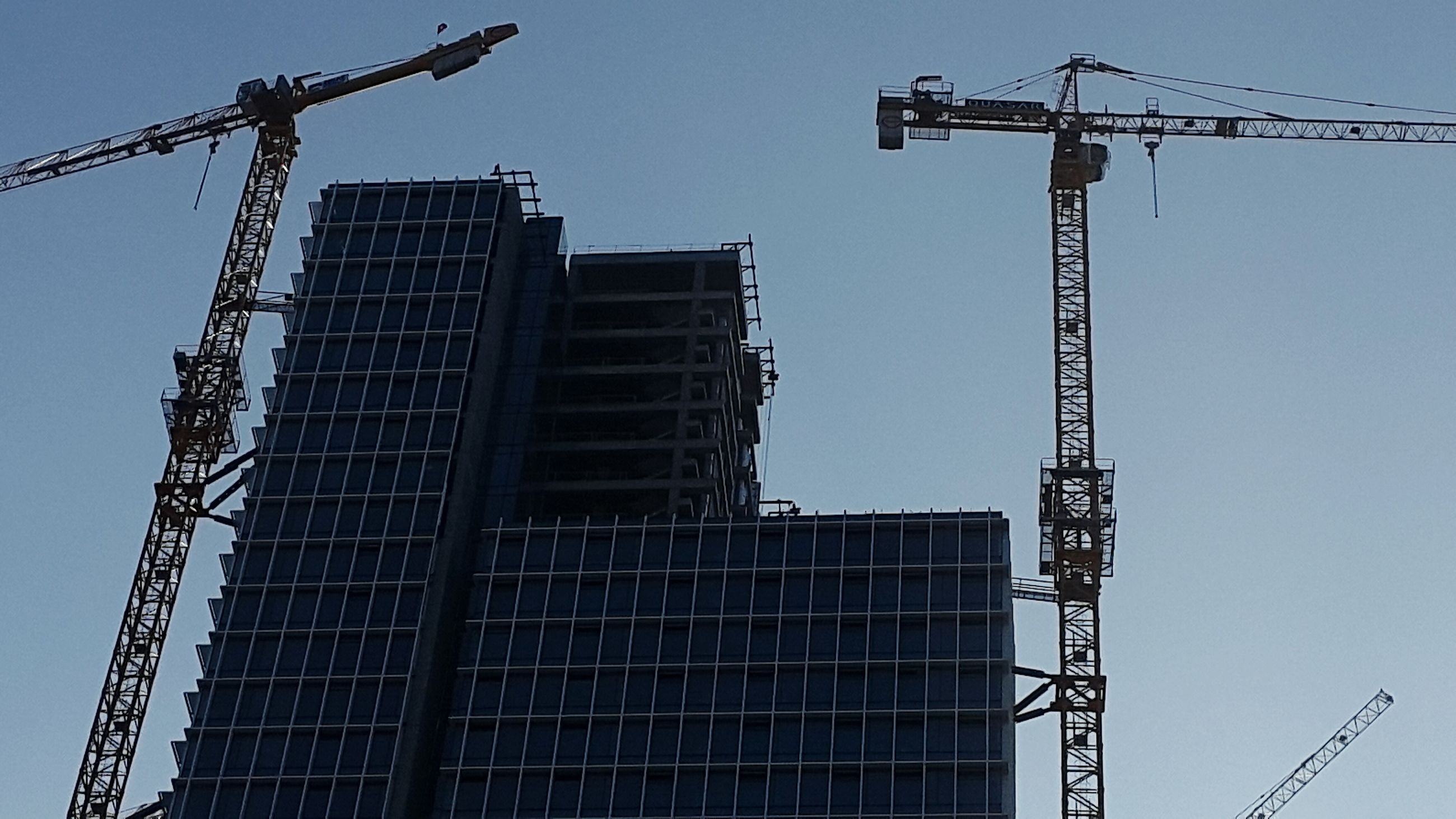 low angle view, construction site, crane - construction machinery, development, clear sky, crane, fuel and power generation, construction, built structure, architecture, technology, building exterior, incomplete, industry, tall - high, construction industry, sky, progress, alternative energy, traditional windmill