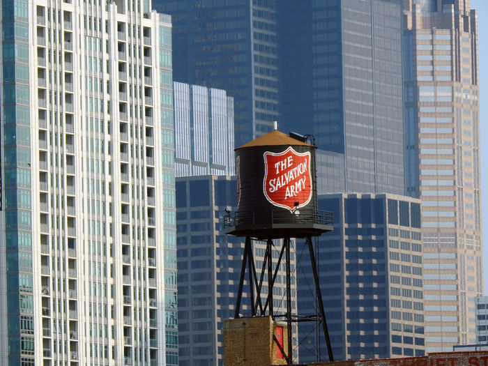 A Salvation Army water tank in downtown Chicago. Salvation Army Architecture Building Building Exterior Built Structure City Communication Day Glass - Material Guidance Low Angle View Modern No People Office Office Building Exterior Outdoors Road Sign Sign Skyscraper Sunlight Text Western Script
