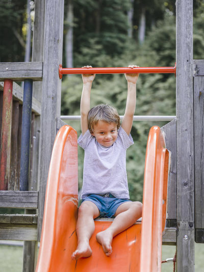 Full length of boy enjoying on slide at playground