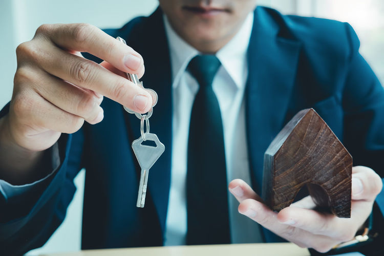 Midsection Of Businessman Holding Model Home And Key While Sitting In Office
