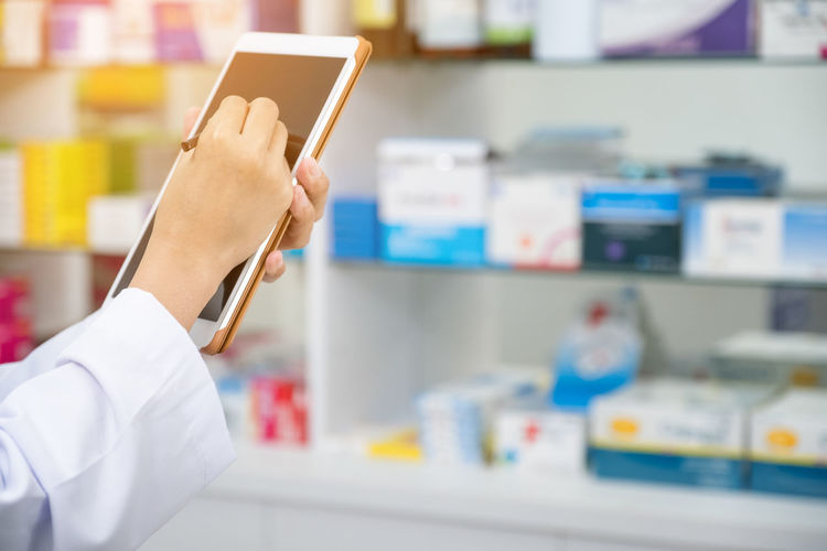 Pharmacist working with a tablet computer in the pharmacy holding it in her hand while reading information Holding Healthcare And Medicine Occupation Indoors  One Person Human Hand Focus On Foreground Pharmacy Lab Coat Medicine Medical Supplies Professional Occupation Hand Prescription Medicine Real People Doctor  Adult Pharmacist Paper