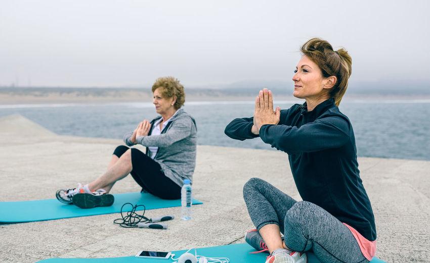 Female friends doing yoga by sea on walkway