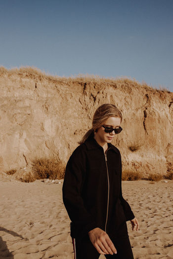 Young woman wearing sunglasses standing on ground
