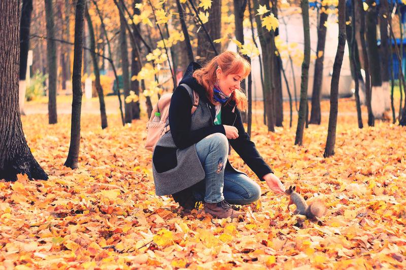 Full length of senior man sitting on leaves in forest
