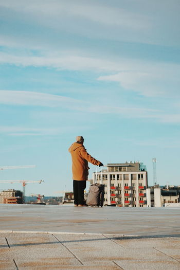 Rear view of man standing on rooftop