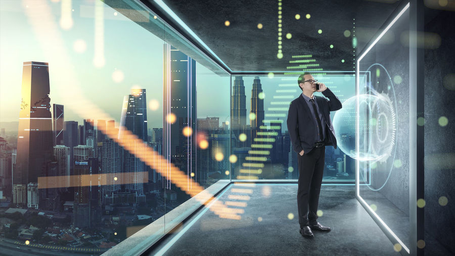 Digital composite image of businessman talking on smart phone while standing by icons in office
