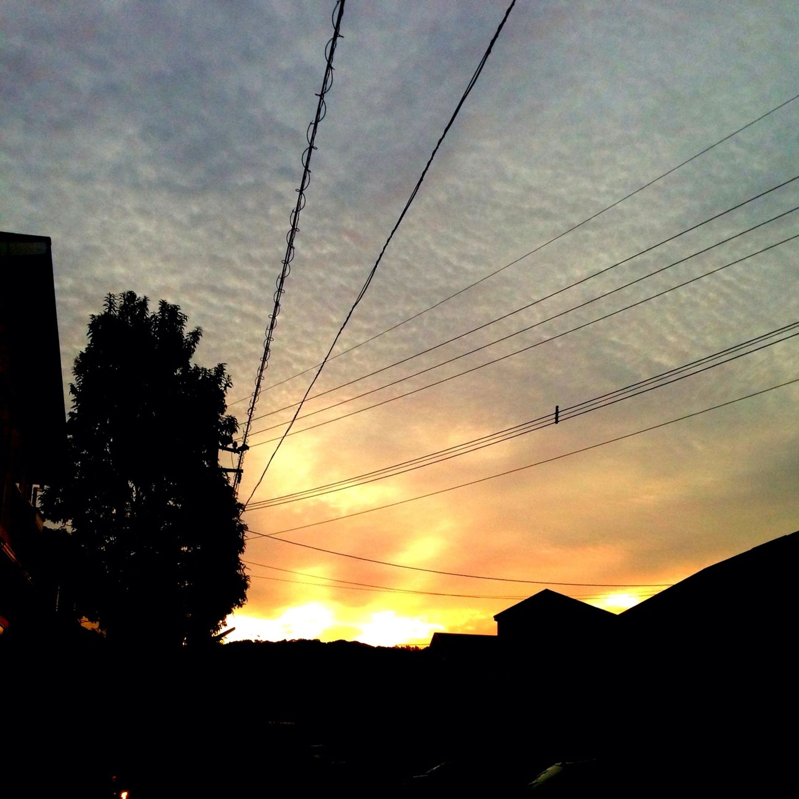 sunset, silhouette, power line, building exterior, built structure, sky, architecture, electricity pylon, cable, orange color, electricity, low angle view, connection, power supply, house, tree, cloud - sky, city, residential structure, power cable