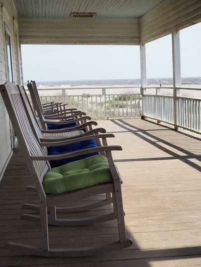 Empty rocking chairs in row on porch