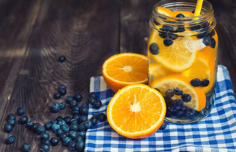 Orange fruits in glass jar on table