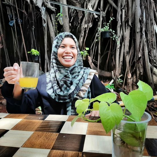 Cheerful woman having drink at outdoor cafe