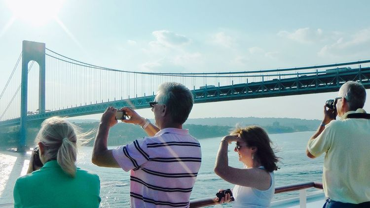 Bridge - Man Made Structure Bridge Over Water Built Structure Casual Clothing City City Life Cloud - Sky Connection Day Family Leisure Activity Lifestyles Outdoors Queen Mary 2, People Looking , Camera, Photos Rear View Relaxation River Sitting Sky Tourism Tourist Travel Destinations Vacations Water