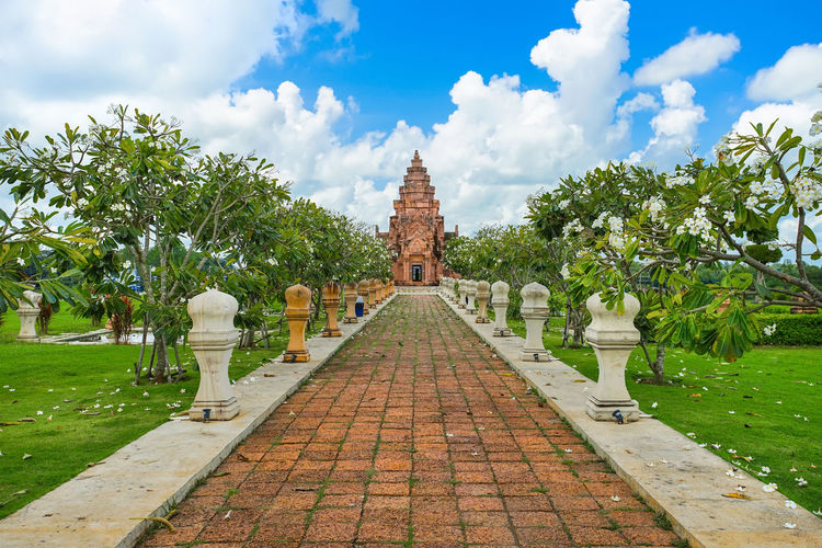 Footpath leading towards temple building against sky