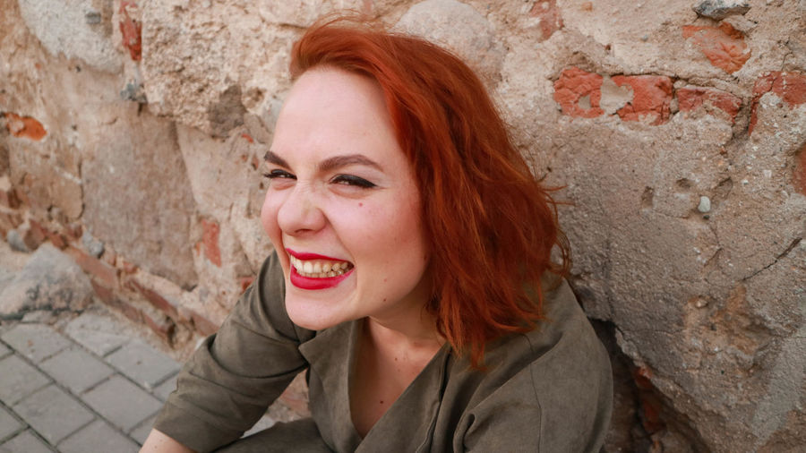 Portrait Of Smiling Redhead Woman Against Wall