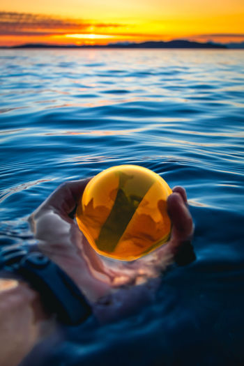 Close-up of hand holding crystal ball in ocean