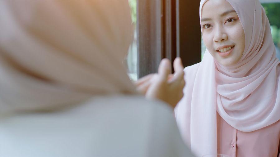 Beautiful young woman in hijab looking at mirror