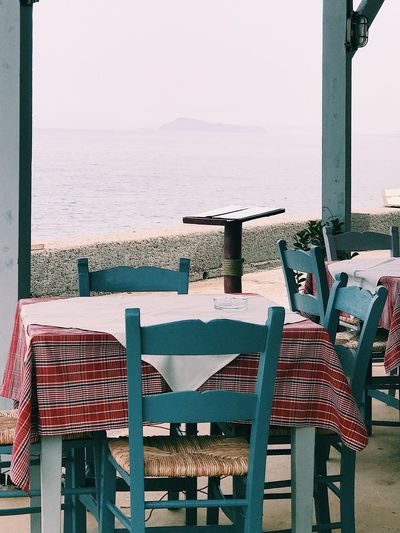 View over the sea from a restaurant in Greece Reservation Empty Seats Empty Chair Empty Seats Front View Sea Idyllic Scenery Wooden Chair Wooden Wood - Material Furnitures Sea Water Seat Sky Nature No People Day Beach Beauty In Nature Wood - Material Chair Horizon Horizon Over Water Empty Table Outdoors Sunlight Land Absence