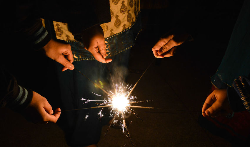 Cropped Image Of People With Lit Sparklers At Night
