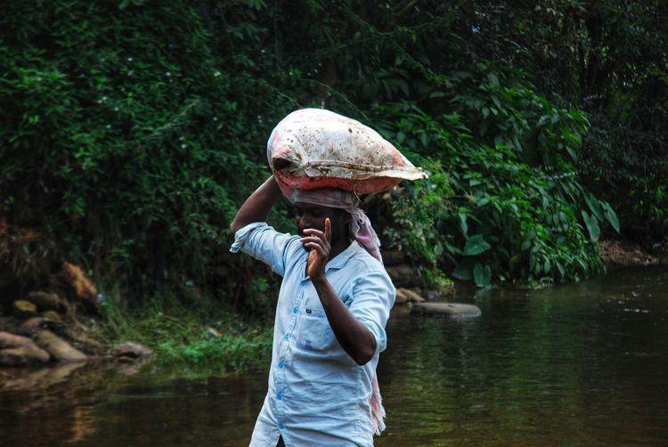 Men holding sandbag on river
