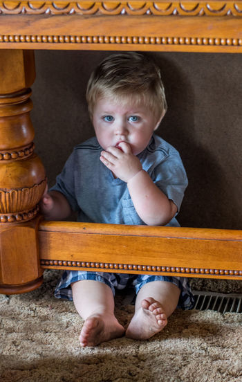Portrait of cute baby boy sitting under table
