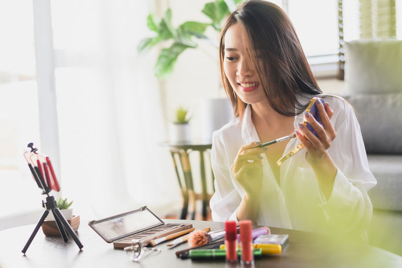 Young woman using phone while sitting on table