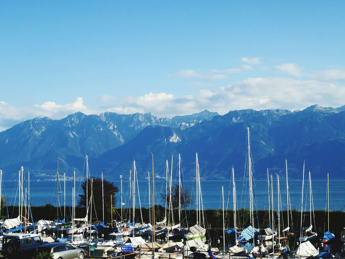 Sailboats moored at harbor against mountains