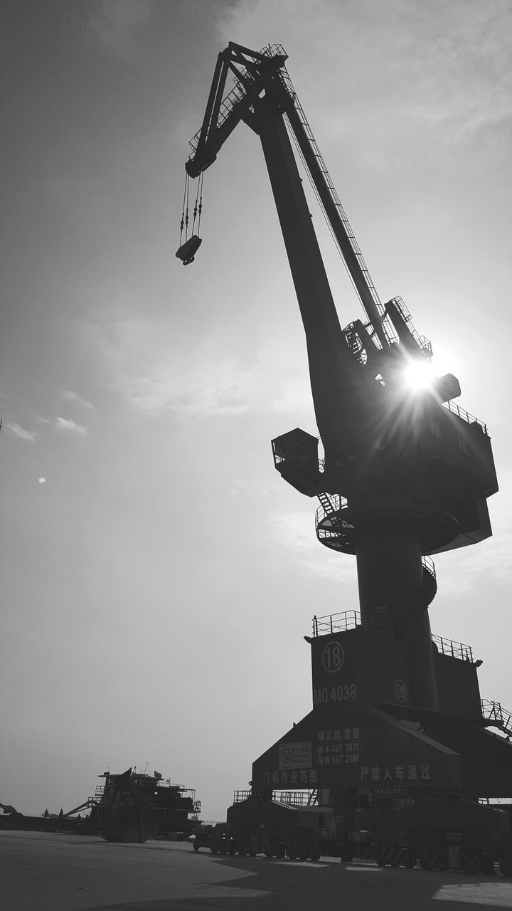 low angle view, sky, cloud - sky, statue, crane - construction machinery, outdoors, sculpture, architecture, no people, building exterior, day