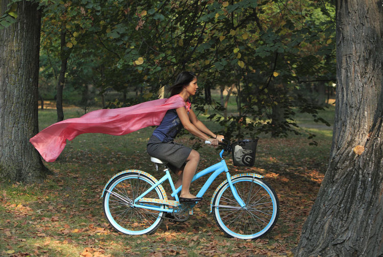 Woman cycling in a park of a city. City Exercise Transportation Woman Bicycle Cycling Girl Leisure Activity Mode Of Transport Motion One Person One Woman Only Outdoors Park - Man Made Space Pink Scarf Ride Riding Scarf Side View Summer Transportation Urban Urban Cycling Urban Transportation Young Adult