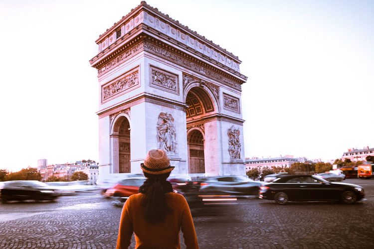 Rear view of woman looking at arc de triomphe on street