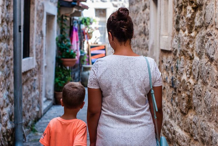 Rear view of mother and son walking in alley