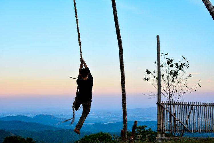 Rear view of man playing on rope against sky