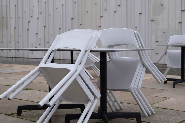 closed EyeEm Selects Chair Seat Absence Empty Day No People Table In A Row Arrangement Focus On Foreground White Color Outdoors Furniture Metal Side By Side Still Life Repetition Relaxation Outdoor Cafe Closed Stacked Chairs And Tables Leaning