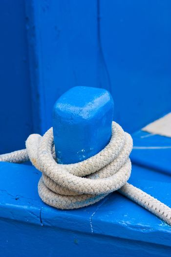 Close-up of rope tied on blue boat