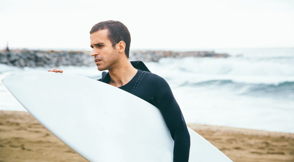 Portrait Of Surfer On Beach Against Sky