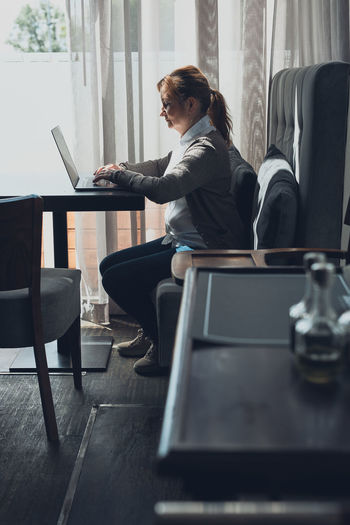 Focused businesswoman working remotely on her laptop computer contemplate managing her work