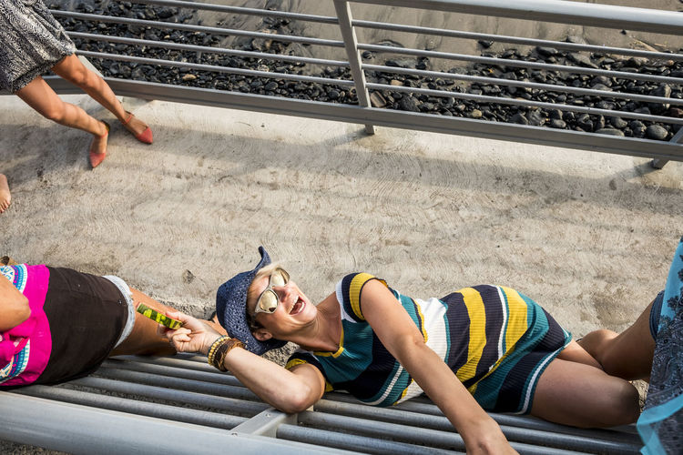 High angle view of friends enjoying by railing at beach