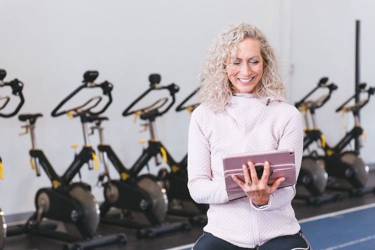 Smiling woman using digital tablet while standing in gym