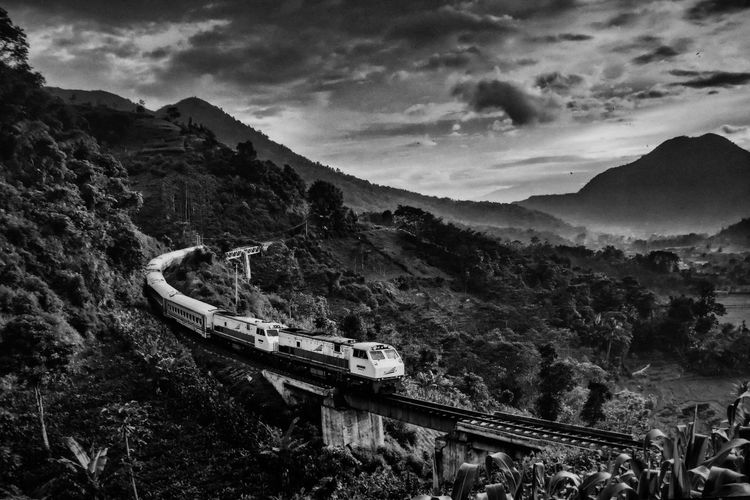 High Angle View Of Train On Railway Bridge By Mountains Against Cloudy Sky