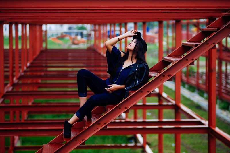 Young woman looking away while lying on ladder