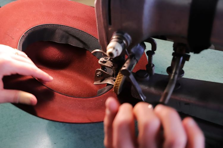 Cropped hands of person working on sewing machine