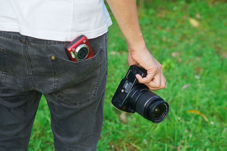 Midsection of man holding camera while standing on field