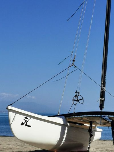 Sailboat moored in sea against clear blue sky